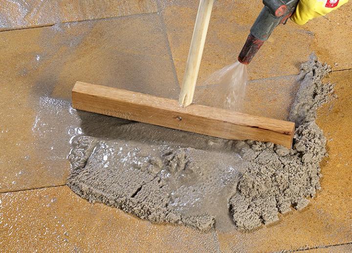 Bild 5: Mörtel mit Hartgummischieber und Wassersprühstrahl einarbeiten